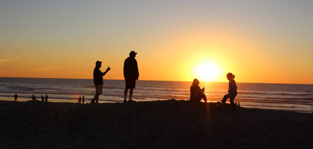 People sitting on a beach looking at sunset