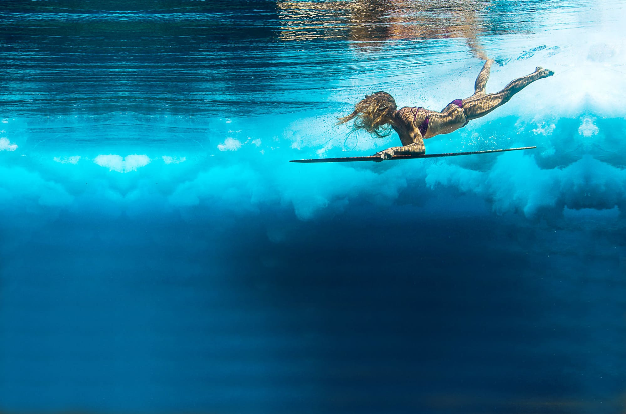 Surfer girl swimming under the sea